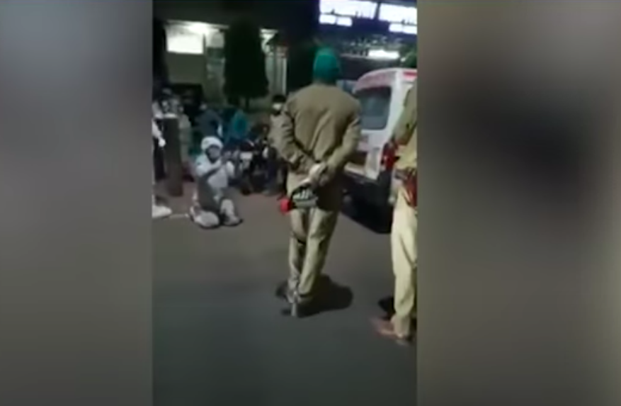 <p>A 22-year-old man in a PPE suit, on his knees, pleading before the Uttar Pradesh police not to take away his mother's oxygen cylinder. Screengrab. </p> (The Lallantop YouTube)
