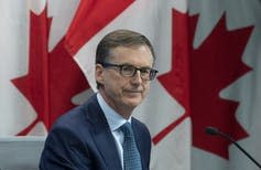 A man wearing glasses with Canadian flags as a backdrop.