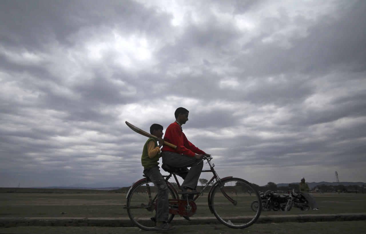 In this Sunday, Feb. 13, 2011 photo, a boy holds a cricket bat and rides a bicycle on the outskirts of Jammu, India. The international cricket landscape has changed dramatically, with India now the commercial powerbase of the sport and the nation of almost 1.2 billion people expecting its team to win a World Cup in the subcontinent.
