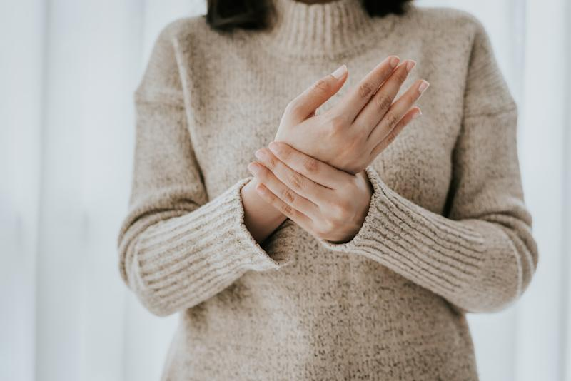 Cropped shot of woman in sweater holding her wrist pain