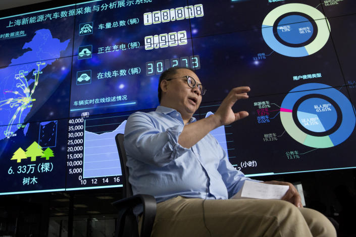In this Friday, June 22, 2018, photo, Ding Xiaohua, deputy director of the Shanghai Electric Vehicle Public Data Collecting, Monitoring and Research Center speaks near a data display screen in Shanghai. According to specifications published in 2016, every electric vehicle in China transmits data from the car's sensors back to the manufacturer. From there, automakers send 61 data points, including location and details about battery and engine function to local centers like the one Ding oversees in Shanghai. (AP Photo/Ng Han Guan)