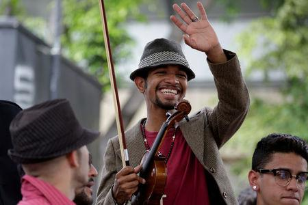 FILE PHOTO - Venezuelan violinist Wuilly Arteaga (C) waves during a gathering against Venezuela's President Nicolas Maduro's government in Caracas, Venezuela June 4, 2017. REUTERS/Marco Bello/File Photo