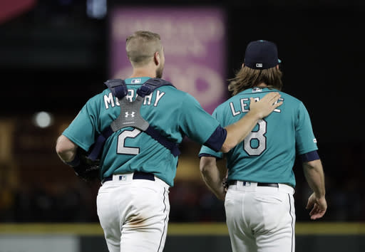 Seattle Mariners starting pitcher Mike Leake, right, walks with catcher Tom Murphy, left, after Leake threw a one-hitter game against the Los Angeles Angels in a baseball game Friday, July 19, 2019, in Seattle. The Mariners won 10-0. (AP Photo/Ted S. Warren)