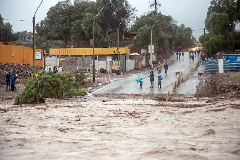 Residents watch the overflowing of the Copiapo River following heavy rainfall in Chile on March 25, 2015
