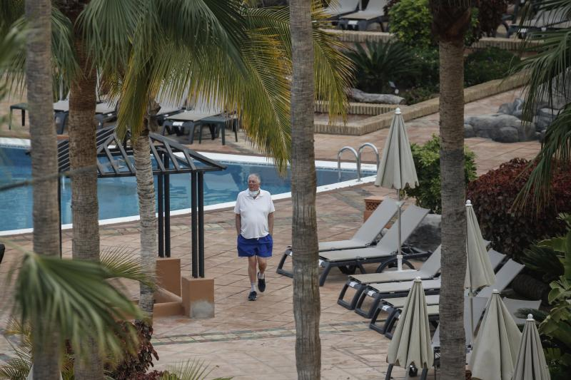 A man walks next the swimming pool of the H10 Costa Adeje Palace hotel in La Caleta, in the Canary Island of Tenerife, Spain, Thursday, Feb. 27, 2020. Spanish officials say a tourist hotel on the Canary Island of Tenerife has been placed in quarantine after an Italian doctor staying there tested positive for the COVID-19 virus and Spanish news media says some 1,000 tourists staying at the complex are not allowed to leave. (AP Photo/Joan Mateu)