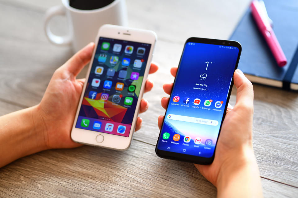 İstanbul, Turkey - March 7, 2018: Hand holding two smart phones on a wooden desk. The smart phones are an Samsung Galaxy S9 plus and iPhone 6 Plus.  Samsung Galaxy is a touchscreen smart phone produced by Samsung Electronics. Apple iPhone 6 plus is a touchscreen smart phone produced by Apple Inc.