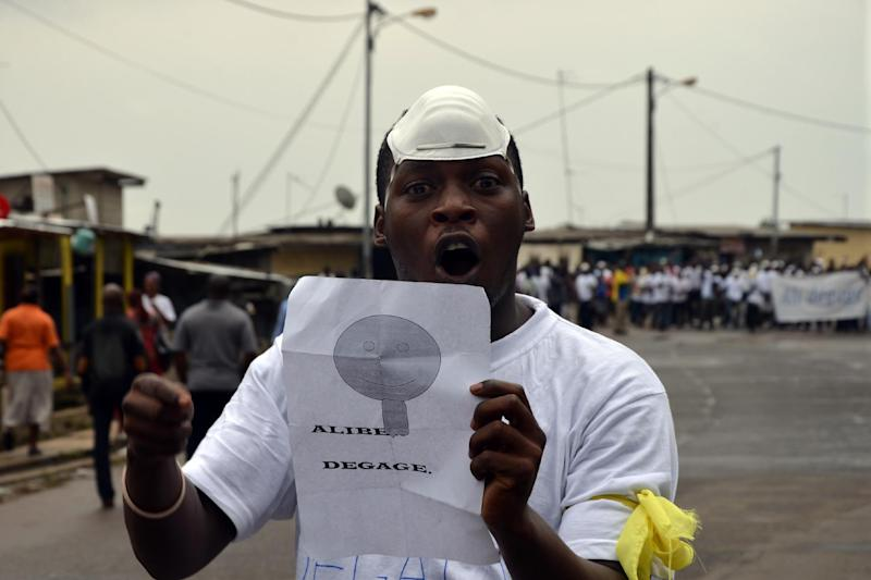 """A protester holds a sign reading """"Ali Ben go away"""" in the Rio district of Libreville on December 20, 2014 during a demonstration (AFP Photo/Celia Lebur)"""