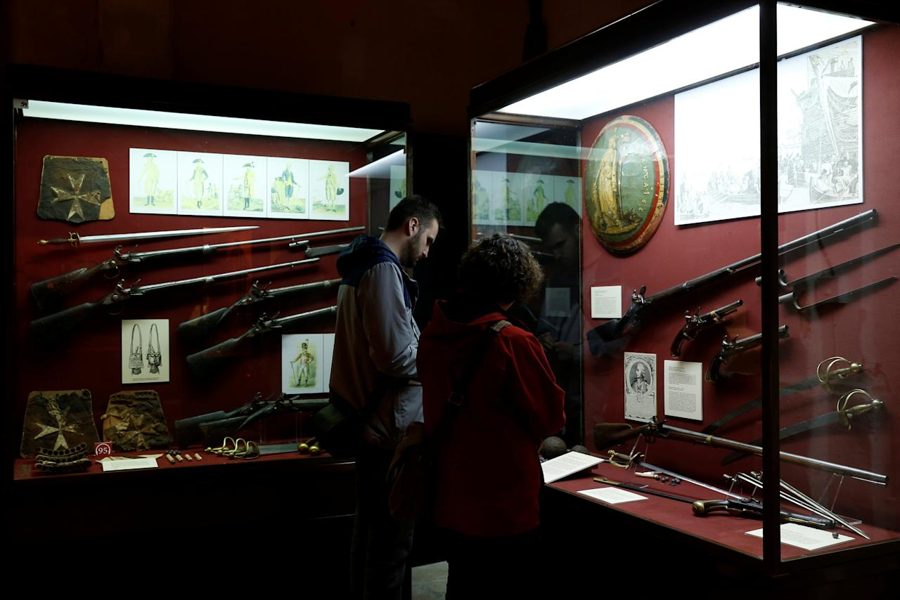 Tourists look at Napoleonic-era French muskets, pistols and swords at the Palace Armoury in Valletta, Malta, March 23, 2018.   REUTERS/Darrin Zammit Lupi