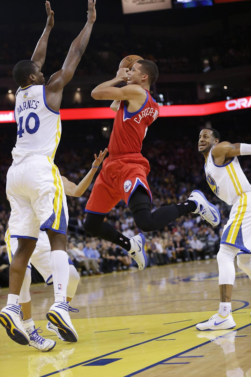 Philadelphia 76ers' Michael Carter-Williams, center, shoots between, Golden State Warriors' Harrison Barnes (40) and Andre Iguodala (9), right, during the first half of an NBA basketball game, Monday, Feb. 10, 2014, in Oakland, Calif. (AP Photo/Marcio Jose Sanchez)