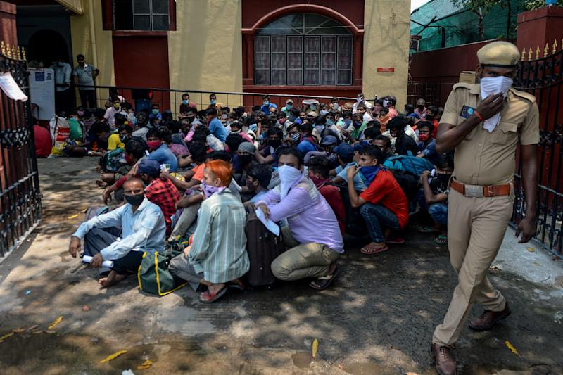 TOPSHOT - Migrant workers and families gather in front of a police station to get transferred to a railway station to board a special train to Bihar state after the government eased a nationwide lockdown imposed as a preventive measure against the COVID-19 coronavirus, in Chennai on May 27, 2020. (Photo by Arun SANKAR / AFP) (Photo by ARUN SANKAR/AFP via Getty Images)