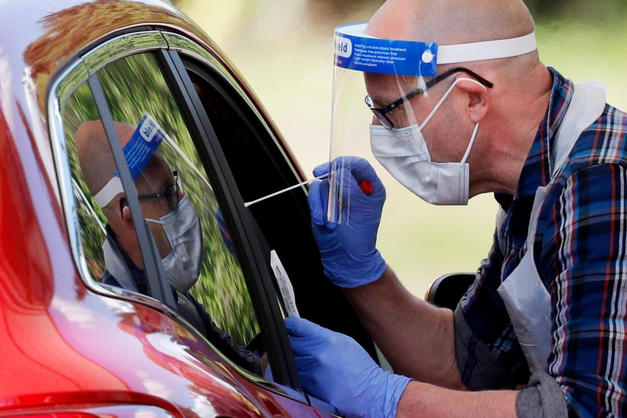 A medical worker takes a swab to test for the novel coronavirus COVID-19 from a visitor to a drive-in testing facility at the Chessington World of Adventures Resort, in Chessington, southwest of London, on May 2, 2020. - Britain's overall death toll from the coronavirus outbreak rose by 739 to 27,510 on May 1 as the government announced that it had reached its COVID-19 testing goal administering a total of 122,347 tests on April 29. (Photo by Adrian DENNIS / AFP) (Photo by ADRIAN DENNIS/AFP via Getty Images)