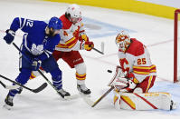 Calgary Flames' goaltender Jacob Markstrom (25) makes a save as Toronto Maple Leafs' Alex Galchenyuk (12) and Rasmus Andersson (4) battle during the second period of an NHL hockey game Tuesday, April 13, 2021 in Toronto. (Frank Gunn/Canadian Press via AP)