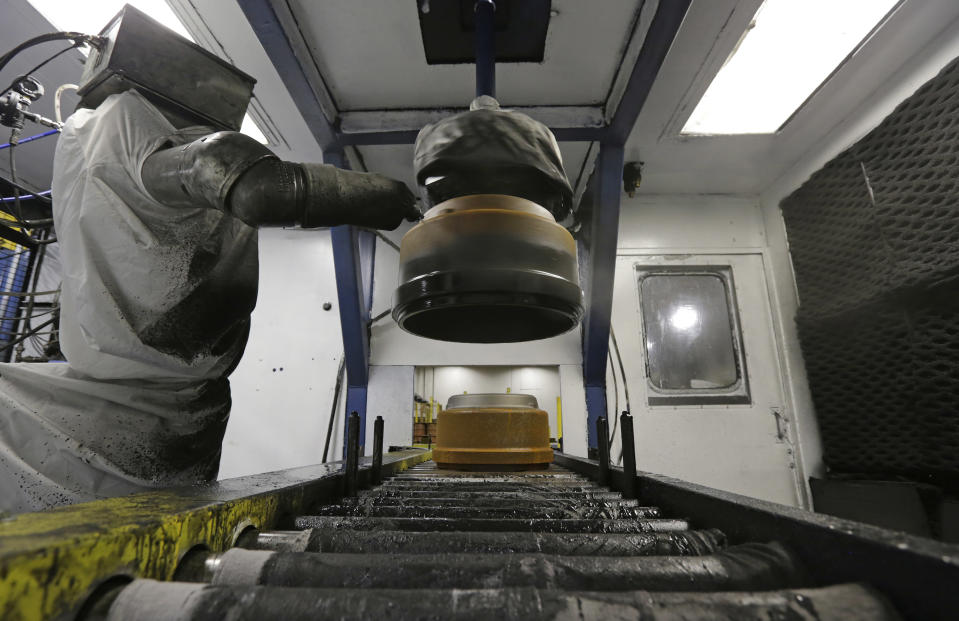 In this Friday, Jan. 11, 2013, photo, a robot paints brake drums at Webb Wheel Products in Cullman, Ala. Webb Wheel hasn't added a factory worker in three years, though it's making 300,000 more drums annually, a 25 percent increase, because of robots. (AP Photo/Dave Martin)