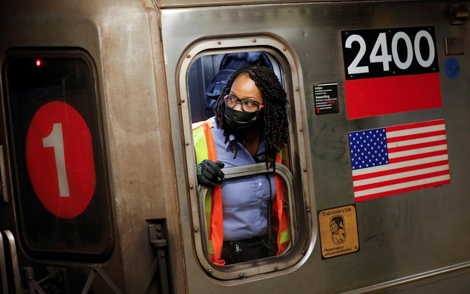 An MTA worker wears a protective mask while working on a subway train - REUTERS/Andrew Kelly