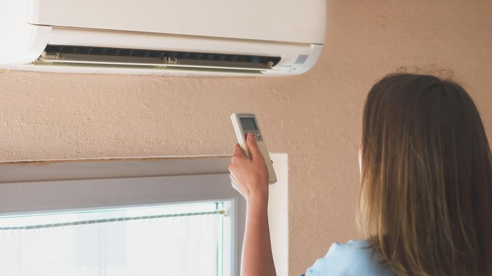 Woman holding remote control aimed at the air conditioner.
