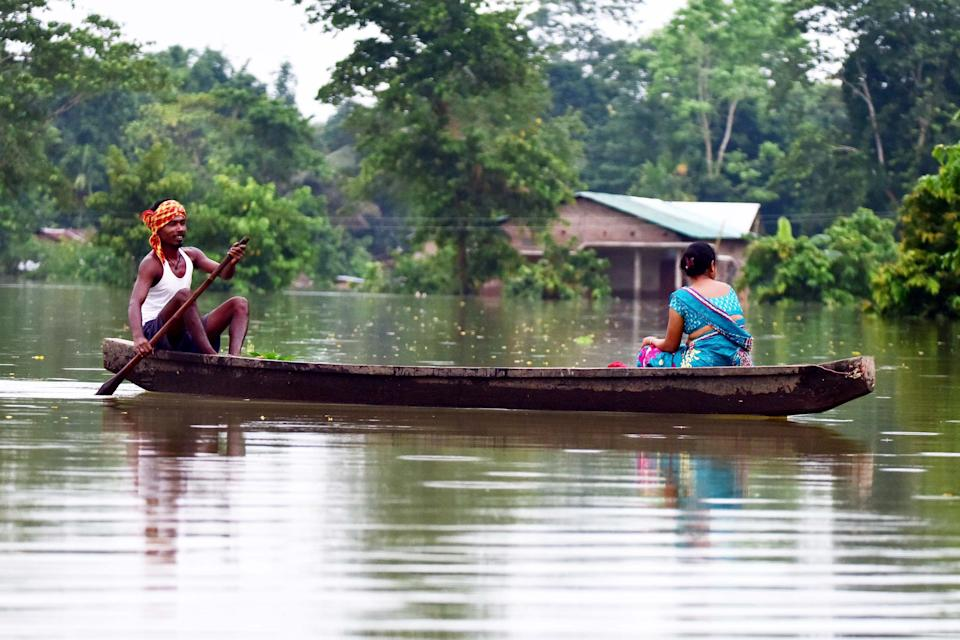 A alood affected family are transported on a boat towards a safer place at Baghmari village in Nagaon District of Assam. (Photo credit should read Anuwar Ali Hazarika/Barcroft Media via Getty Images)