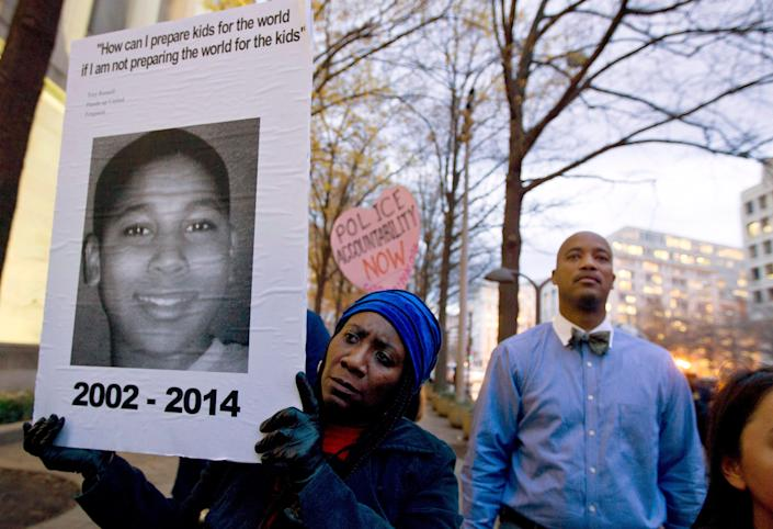 In this Dec. 1, 2014 file photo, Tomiko Shine holds up a poster of Tamir Rice during a protest in Washington. The 12-year-old black boy was fatally shot by a white Cleveland police officer near a gazebo in a recreational area in November 2014. Officers were responding to a report of a man waving a gun. The boy had a pellet gun tucked in his waistband and was shot right after their cruiser skidded to a stop, just feet away.