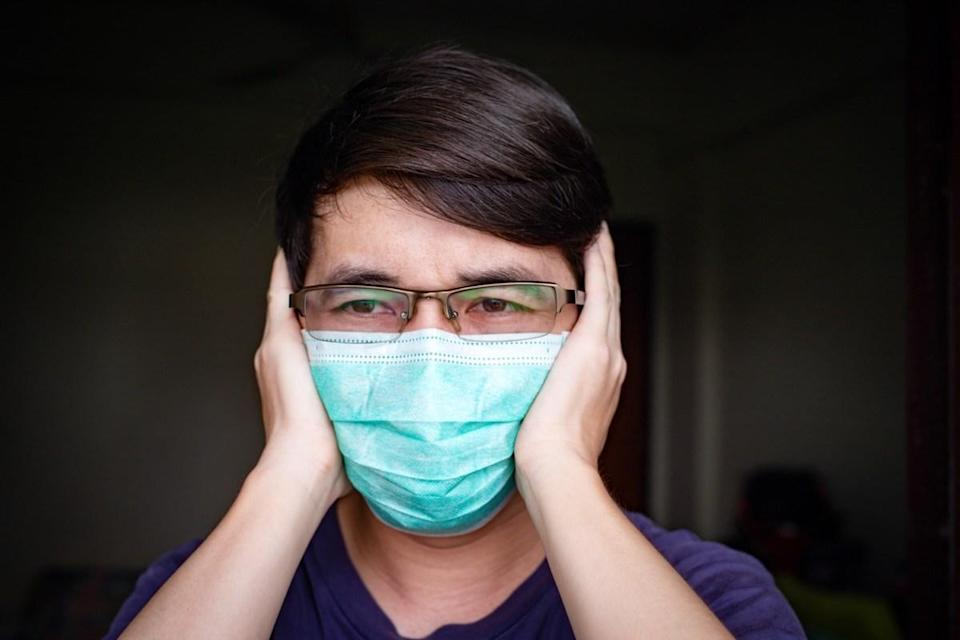 man with eyeglasses wearing hygienic mask feeling headache