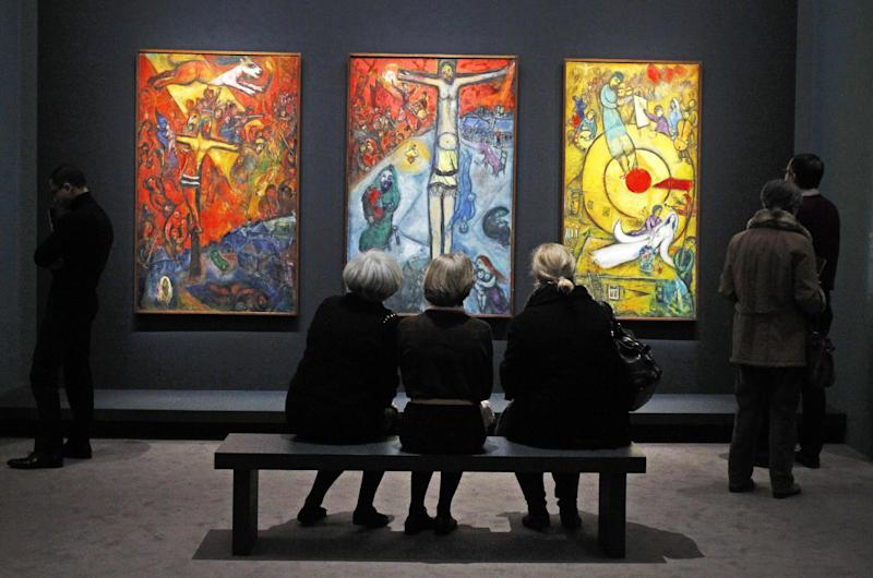 Members of the media view a triptych by Russian artist Marc Chagall before the opening of the exhibition: Chagall, between War and Peace, at the Luxembourg museum in Paris, Tuesday Feb. 19, 2013. The exhibition starts February 21 and ends July 21, 2013. Paintings are from left: 1937, Resistance, 1948, Resurrection, 1952, Liberation.(AP Photo/Remy de la Mauviniere)