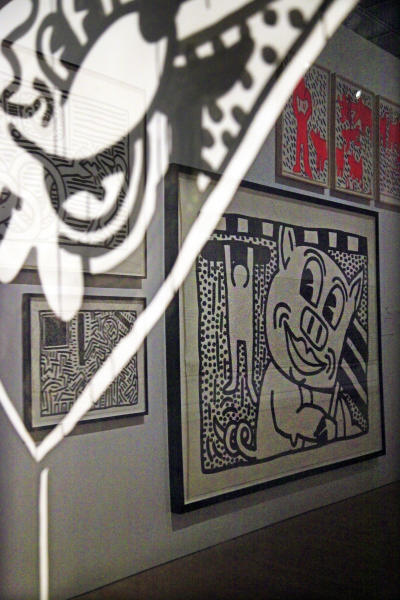 """In this March 14, 2012 photo, a cross-reflection of installations of art by Keith Haring is shown before the opening of the exhibition """"Keith Haring: 1978-1982"""" at the Brooklyn Museum in New York. The exhibition chronicles the period in Haring's career from his arrival in New York through the years making public and political art on city streets. (AP Photo/Bebeto Matthews)"""