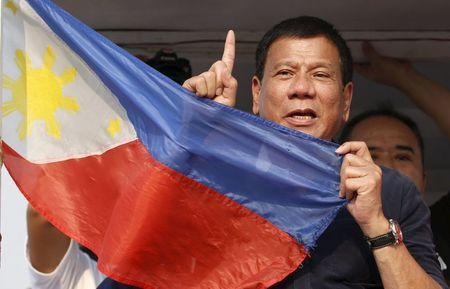 """Presidential candidate Rodrigo """"Digong"""" Duterte holds the national flag during election campaigning for May 2016 national elections in Malabon, Metro Manila in the Philippines April 27, 2016. REUTERS/Erik De Castro"""