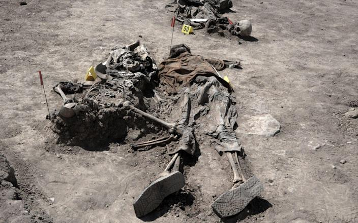 Human remains, reportedly of victims of the 2014 Badush prison massacre, are unearthed from a mass grave - ZAID AL-OBEIDI/AFP