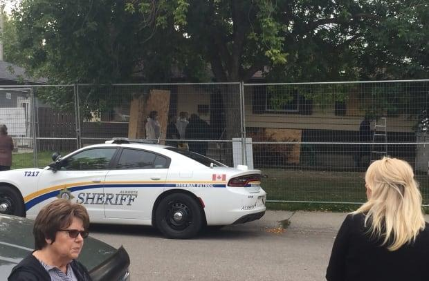 Neighbours watch as provincial sheriffs close down 2000 Cottonwood Crescent S.E. It's been shut a record three times now by the SCAN team. (Seth Barlow - image credit)
