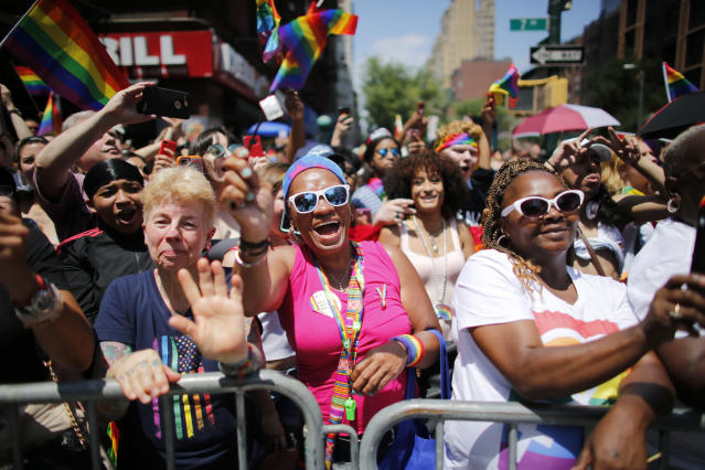 <p>Revelers standing on Seventh Avenue watch the annual Pride Parade on June 24, 2018 in New York City. (Photo: Kena Betancur/Getty Images) </p>