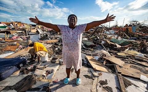 "Aliana Alexis, of Haiti, stands on the concrete slab of what is left of her home after destruction from Hurricane Dorian in an area called ""The Mud"" at Marsh Harbour in Great Abaco Island - Credit: Al Diaz/Miami Herald / AP"