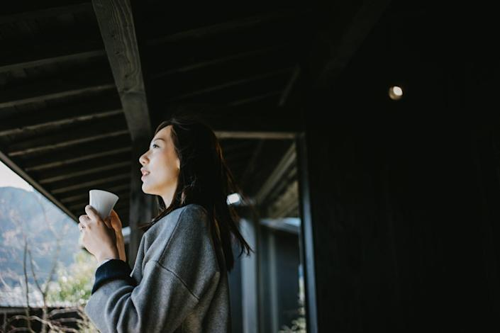 Beautiful young Asian woman drinking coffee and relaxing on balcony on a fresh bright morning
