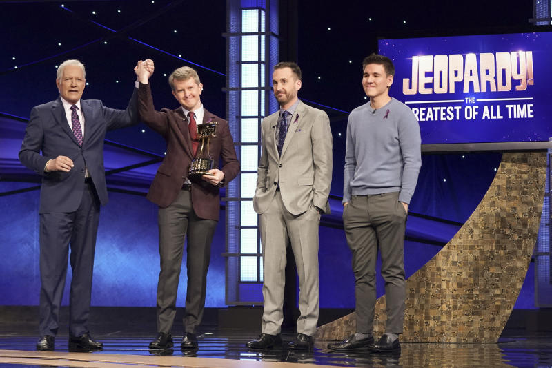 "This image released by ABC shows host Alex Trebec, left, joining hands with contestant Ken Jennings after he won ""JEOPARDY! The Greatest of All Time,"" as fellow contestants Brad Rutter and James Holzhauer look on.  Jennings won the $1 million prize in the tournament that stretched out over four entertaining nights on ABC's prime-time schedule. (Eric McCandless/ABC via AP)"