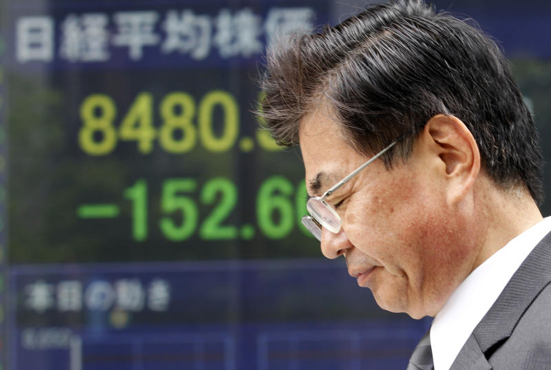A man walks by the electronic stock board of a securities firm in Tokyo Thursday, May 31, 2012. Japan's Nikkei 225 index shed 158.62 points, or 1.84 percent, from Wednesday to end the morning session at 8,474.57. (AP Photo/Koji Sasahara)