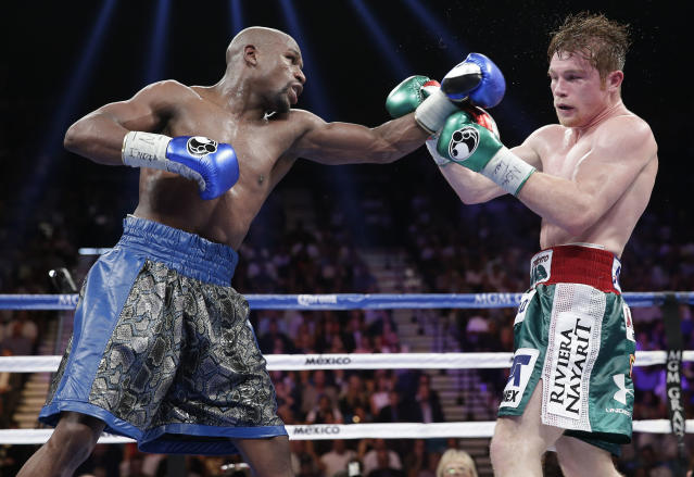 Floyd Mayweather Jr. (L) lands a jab on Canelo Alvarez during their 2013 bout that Mayweather won by decision. (AP)