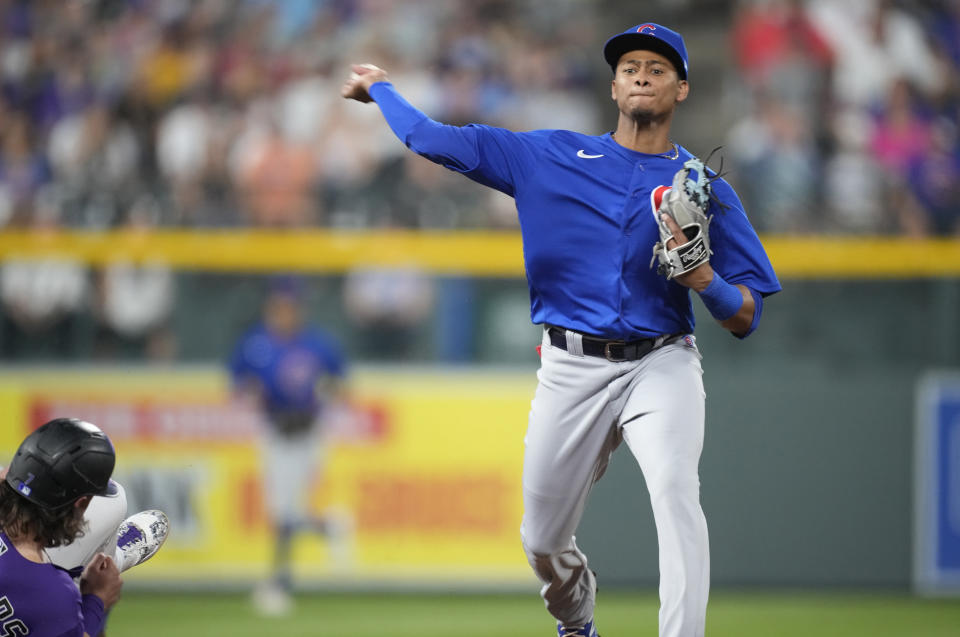 Chicago Cubs shortstop Sergio Alcantara, right, throws to first base after forcing out Colorado Rockies' Brendan Rodgers at second base on the front end of a double play hit into by Charlie Blackmon to end the fifth inning of a baseball game Wednesday, Aug. 4, 2021, in Denver. (AP Photo/David Zalubowski)