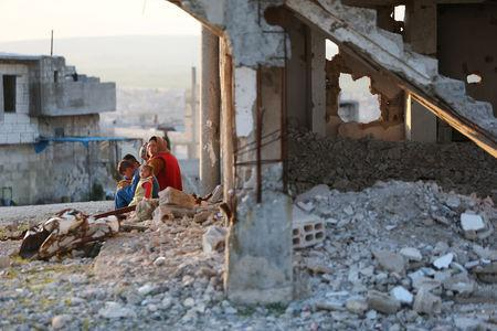 A woman sits with children on a rubble from damaged buildings in Kobani, Syria April 3, 2019. REUTERS/Ali Hashisho