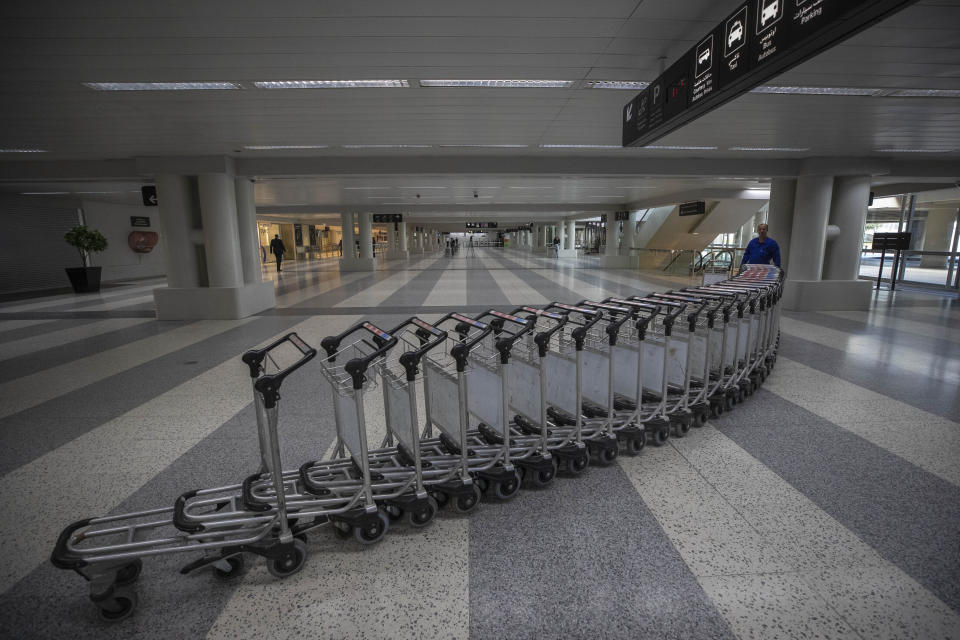FILE - In this March 19, 2020 file photo, a worker pushes trollies at an empty terminal hall of the Rafik Hariri International Airport, in Beirut, Lebanon. On Wednesday, July 1, 2020, Beirut's airport is partially reopening after a three-month shutdown and Lebanon's cash-strapped government hopes thousands of Lebanese expatriates will return for the summer, injecting badly needed dollars into the sinking economy. (AP Photo/Hassan Ammar, File)