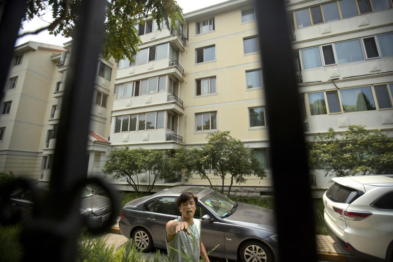 FILE - In this July 14, 2017, file photo, a plainclothes Chinese security guard attempts to stop a photographer from taking photos of an apartment building where Liu Xia, the wife of Chinese dissident and Nobel Prize winner Liu Xiaobo, had been living under house arrest in Beijing. A person briefed on the matter said Tuesday, July 10, 2018, that Liu Xia, the widow of Chinese Nobel Peace Prize Laureate Liu Xiaobo, has left China for Europe after eight years under house arrest. (AP Photo/Mark Schiefelbein, File)