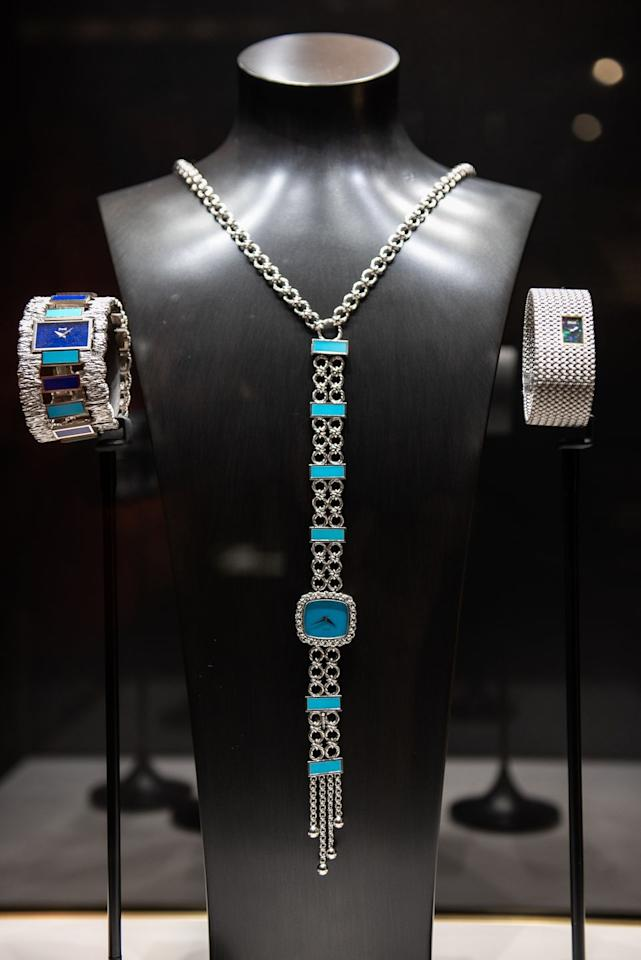 <p>A white gold necklace watch with a turquoise dial and plates from 1973, displayed with two watches on the sides. </p>