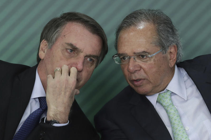 Brazil's President Jair Bolsonaro, left, talks with Economy Minister Paulo Guedes, at the Planalto Presidential Palace, in Brasilia, Brazil, Monday, April 8, 2019. Bolsonaro sanctioned the Positive Registration Law, which will gather information from all Brazilian consumers, facilitating access to credit and reducing interest rates. (AP Photo/Eraldo Peres)