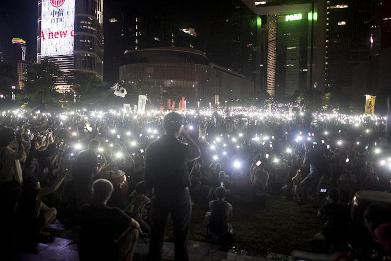 Pro-democracy activist Chan Kin-Man (C) looks out at protesters waving their mobile phones during a pro-democracy rally next to the Hong Kong government complex on August 31, 2014