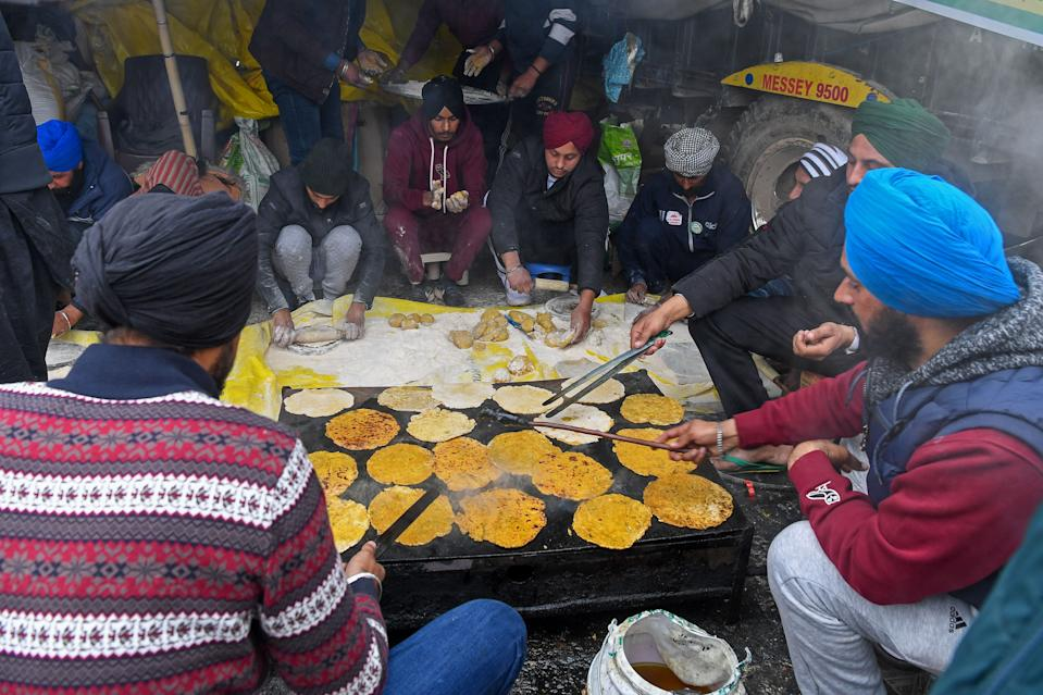 Volunteers cook breakfast as farmers continue to demonstrate against the central government's recent agricultural reforms while blocking a highway at the Delhi-Haryana state border in Singhu on December 30, 2020. (Photo by PRAKASH SINGH/AFP via Getty Images)