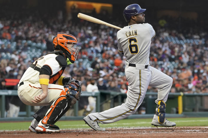 Milwaukee Brewers' Lorenzo Cain (6) watches his two-run single in front of San Francisco Giants catcher Buster Posey during the second inning of a baseball game in San Francisco, Wednesday, Sept. 1, 2021. (AP Photo/Jeff Chiu)
