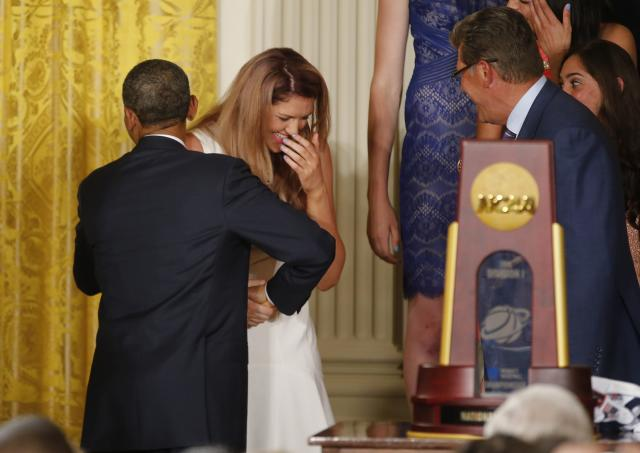U.S. President Barack Obama hugs and shakes the hand of UConn women's basketball star Stefanie Dolson (C) as UConn women's coach Geno Auriemma (R) looks on after Dolson fell off the stage during a ceremony honoring the NCAA basketball champion University of Connecticut Huskies men's and women's basketball teams in the East Room of the White House in Washington, June 9, 2014. Dolson was uninjured in the fall. REUTERS/Jim Bourg (UNITED STATES - Tags: POLITICS SPORT BASKETBALL)
