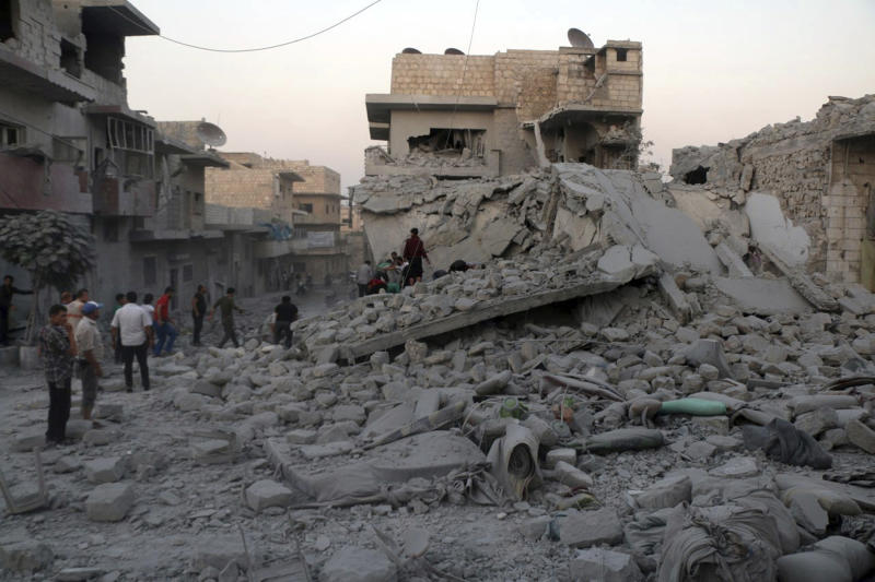 This photo released Wednesday, Aug. 28, 2019 by the opposition Syrian Civil Defense rescue group, also known as White Helmets, which has been authenticated based on its contents and other AP reporting, shows people searching for victims under the rubble of destroyed buildings that was hit by airstrikes in the northern town of Maaret al-Numan, in Idlib province, Syria. Idlib is the Syrian opposition's final stronghold. The opposition Syrian Civil Defense group of first responders said airstrikes on Maaret al-Numan on Wednesday killed 12 people and wounded 34. (Syrian Civil Defense White Helmets via AP)
