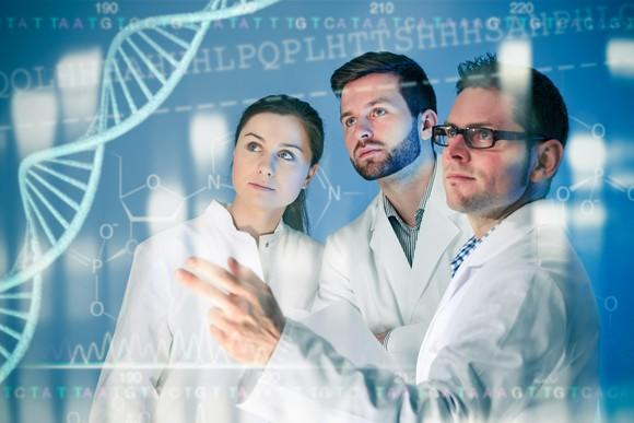 Researchers in lab coats look at an image of a double helix projected on a screen in front of them.