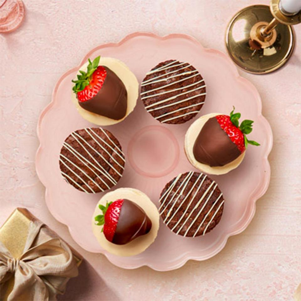 """<p>Sure, everyone loves Edible's famous chocolate-covered strawberries, but this year they are debuting new treats from their Bakeshop. We're partial to this <a href=""""https://www.ediblearrangements.com/fruit-gifts/valentine-s-day-cheesecake-chocolate-box-6939?t=1610563907661&ArrangementGroupID=5"""" rel=""""nofollow noopener"""" target=""""_blank"""" data-ylk=""""slk:yummy box"""" class=""""link rapid-noclick-resp"""">yummy box</a> featuring brownies, cheesecake and, of course, strawberries. You'll be sure to impress with this sweet twist on the classic.</p> <p><strong>$49.99, <a href=""""https://www.ediblearrangements.com/fruit-gifts/valentine-s-day-cheesecake-chocolate-box-6939?t=1610563907661&ArrangementGroupID=5"""" rel=""""nofollow noopener"""" target=""""_blank"""" data-ylk=""""slk:ediblearrangements.com"""" class=""""link rapid-noclick-resp"""">ediblearrangements.com</a></strong></p>"""