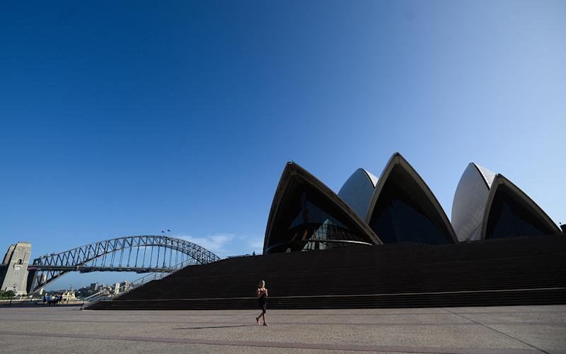 A woman walking in front of a nearly deserted Sydney Opera House. Source: AAP