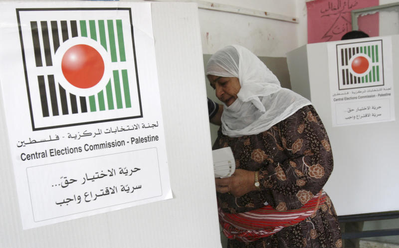 A Palestinian woman prepares to vote in municipal elections at a polling station in the West Bank city of Nablus, Saturday, Oct. 20, 2012. Palestinians vote for mayors and local councils in 93 communities across the West Bank on Saturday--their first chance to cast ballots in six years. (AP Photo/Nasser Ishtayeh)