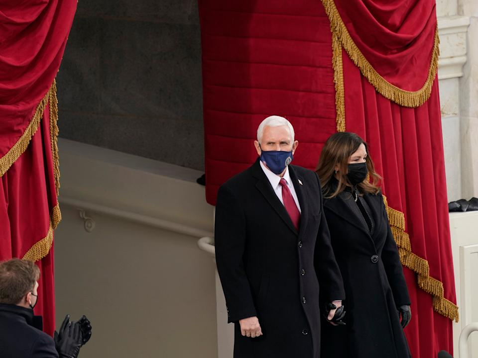 Vice President Mike Pence and Karen Pence arrive at the inauguration of Joe Biden on the West Front of the US Capitol. Mr Pence is attending the inauguration ceremony despite the absence of President Donald Trump, who left Washington before the ceremony beganAP