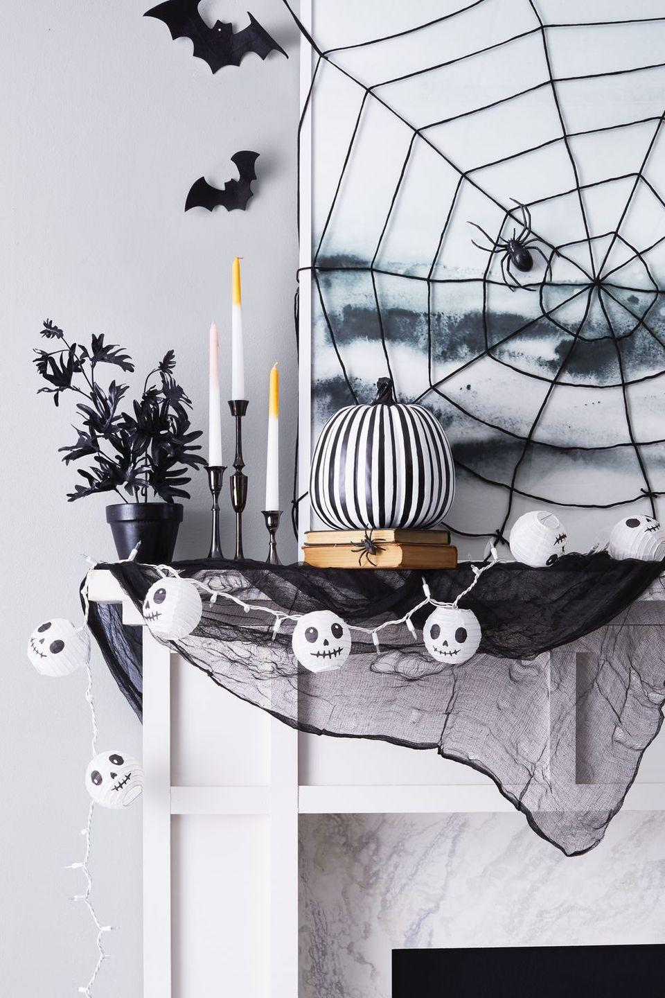 <p>Amp up a cobweb-covered mantel with a pumpkin decked out in black-and-white stripes. Pull the look together with candlesticks and string lights — with skulls, of course. </p>